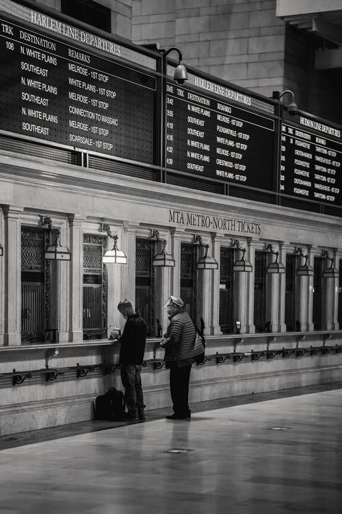 Black and white of faceless people standing near ticket window in railway station with classic interior